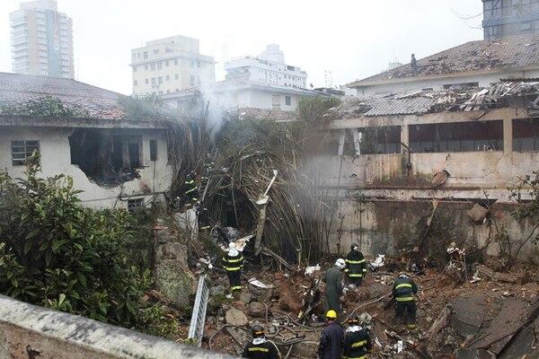Bomberos trabajan en el lugar donde se estrelló el avión ejecutivo en el cual viajaba el candidato presidencial Eduardo Campos. La nave cayó en un área residencial en la ciudad portuaria de Santos.   AP