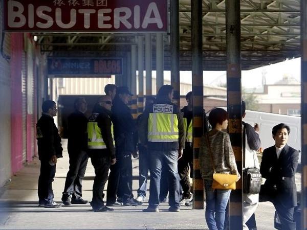 La Policía Nacional y ciudadanos chinos durante el registro en el polígono industrial Cobo Calleja.   EFE