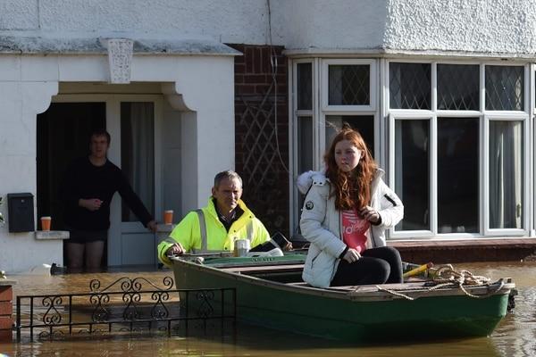 Residentes son rescatados de sus hogares en un bote en medio de las inundaciones en Hereford, en el oeste de Inglaterra, el 17 de febrero del 2020, después de la tormenta Dennis. Foto: AFP