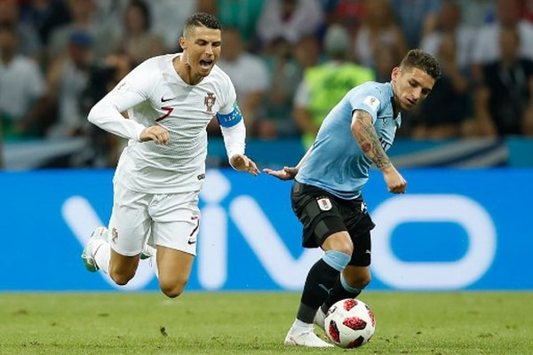 Prohibido el paso. El volante de Uruguay, Lucas Torreira, frena con falta al luso Cristiano Ronaldo. El astro portugués no tuvo un día fácil ante la férrea zaga suramericana. Fotografía: AFP