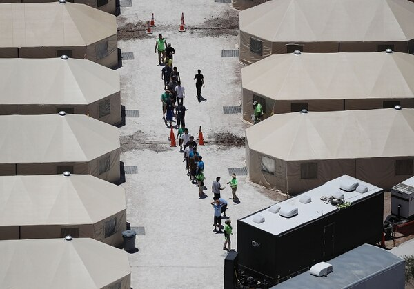 Niños y trabajadores son vistos en un campamento de tiendas de campaña construido recientemente cerca del puerto de entrada de Tornillo el 19 de junio de 2018 en Tornillo, Texas. La administración Trump está utilizando esas instalaciones para albergar a niños inmigrantes separados de sus padres después de ser atrapados ingresando al país ilegalmente. AFP