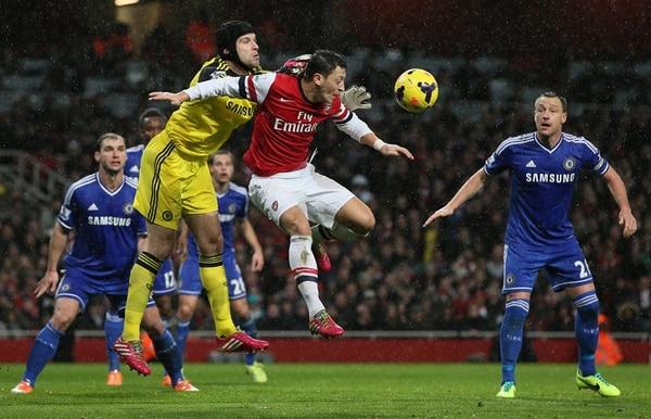 Petr Cech, guardameta del Chelsea, se anticipa a Mesut Ozil, del Arsenal, en el partido jugado en el Emirates Stadium. Observa John Terry.   AP