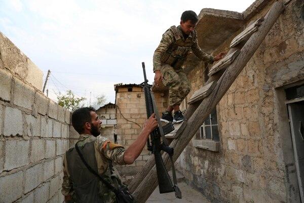 Combatientes sirios respaldados por Turquía suben al techo de una casa en la ciudad fronteriza de Ras al-Ain, el 19 de octubre del 2019. Foto: AFP