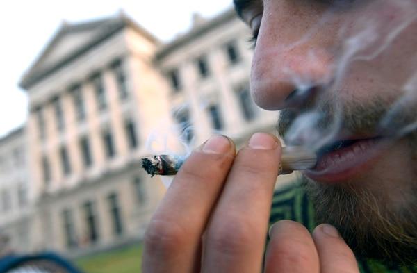 Un joven fumó marihuana el miércoles en las afueras del Congreso en Montevideo, donde se votó el proyecto. | AP.