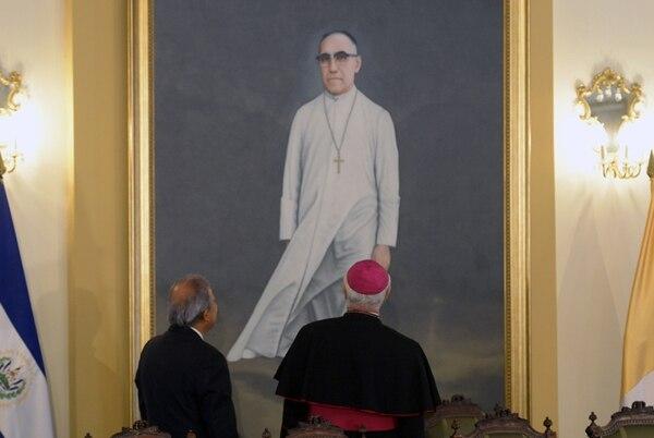 Sánchez y Vincenzo Plagia observan un retrato de Romero.   AFP