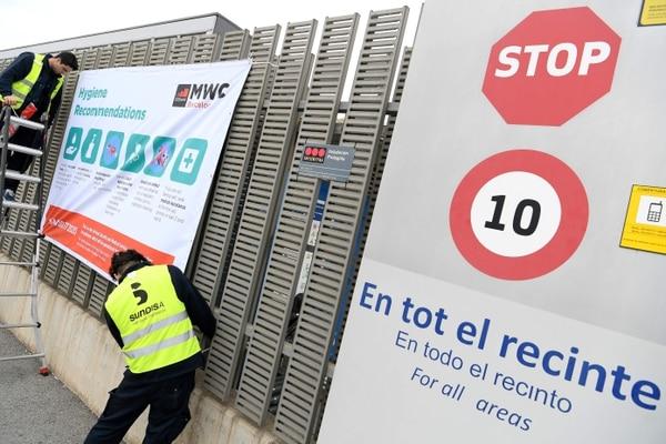 Trabajadores limpian las ventanas en una de las entradas del Congreso Mundial del Móvil 2020 en Barcelona, España, el martes 11 de febrero de 2020, un día antes de su cancelación. (Foto: Lluis Gene / AFP)
