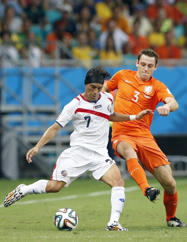 Christian Bolaños (izq.) ante el holandés Stefan de Vrijs, el 5 de julio en Salvador, Brasil. El volante ya había disputado tres Mundiales de la FIFA. | EFE