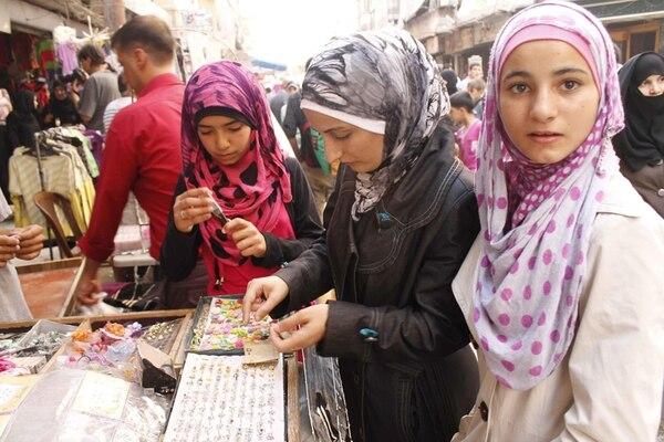 Jóvenes sirias comprando en puesto de calle en la ciudad siria de Alepo, cuando la población del país intenta regresar a la normalidad. Los sirios confían en que el acuerdo ruso-estadounidense permita lograr la paz. | EFE