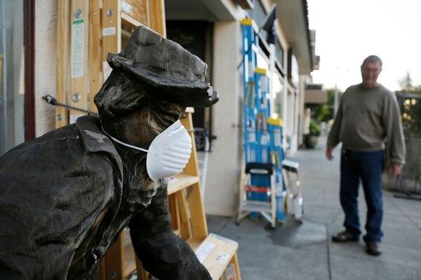 Una escultura lleva una mascarilla, en las afueras de una ferretería en Sausalito, California, Estados Unidos. Foto: AP Photo / Eric Risberg.