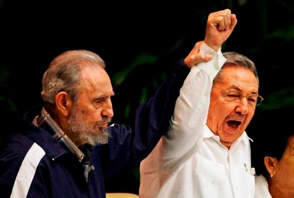En esta foto del 19 de abril de 2011, Fidel Castro, a la izquierda, levanta la mano de su hermano, el presidente cubano Raúl Castro, mientras cantan el himno del socialismo internacional durante el VI Congreso del Partido Comunista en La Habana, Cuba. A medida que se acercaban a los 80 y 90 años, los Castro y sus compañeros arrojaron una sombra tan profunda que los cubanos nacidos en las primeras décadas después de la revolución se conocieron como la