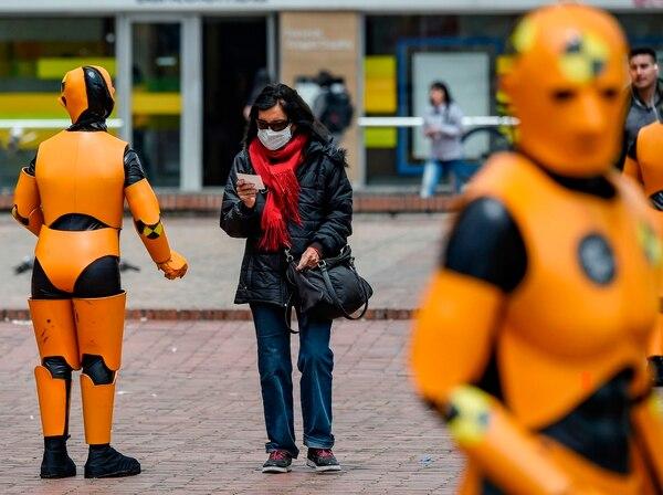 Una mujer usa una mascarilla protectora como precaución contra la propagación del nuevo coronavirus, covid-19, camina junto al personal de tráfico con trajes de robot de seguridad vial, en Bogotá. Foto de AFP