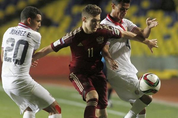 Eduardo Juárez e Ian Smith intentan quitarle la pelota a Alexander Lomovitskiy, de Rusia, en el segundo juego de la fase de grupos, el cual terminó igualado a una anotación. | AFP