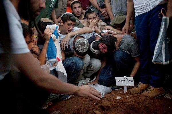 Familiares y amigos de Eyal Yifrah, Gilad Shaar y Naftali Fraenkel, los tres jóvenes secuestrados, manifiestan su dolor sobre la tumba del primero durante el funeral este martes en Modiin, Israel.