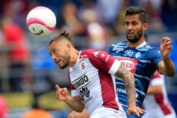El atacante David Ramírez (blanco) remata de cabeza, pese a la marca del brumoso Rándall Alvarado (azul), durante el juego en el que Saprissa se impuso 3 a 4 en el Fello Meza.