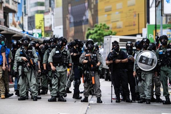 Policías antidisturbios resguardan una carretera mientras los manifestantes asisten a una protesta en favor de la democracia contra una nueva ley de seguridad propuesta por China, el 24 de mayo del 2020. Foto: AFP