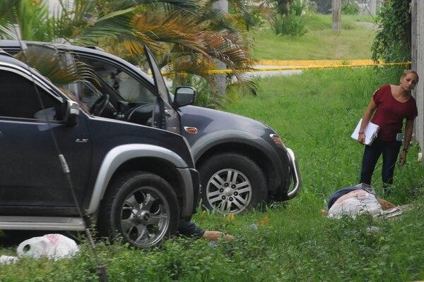 Una funcionaria de medicina forense participa en el levantamiento de los cadáveres frente a la Morgue Judicial de San Pedro Sula.   AFP