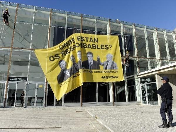 Hoy, militantes de Greenpeace desplegaron en la fachada del Palacio de Exposiciones de La Coruña, donde tiene lugar el juicio un gran pancarta amarilla con las palabras