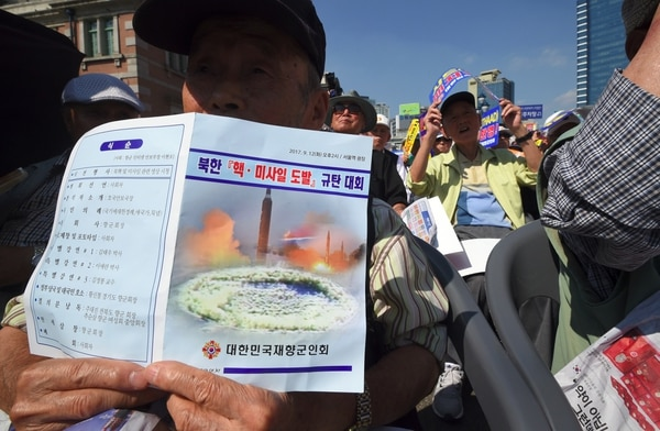 Miembros de la Asociación de Veteranos de Corea sostienen pancartas durante una manifestación exigiendo el despliegue de armas nucleares tácticas.