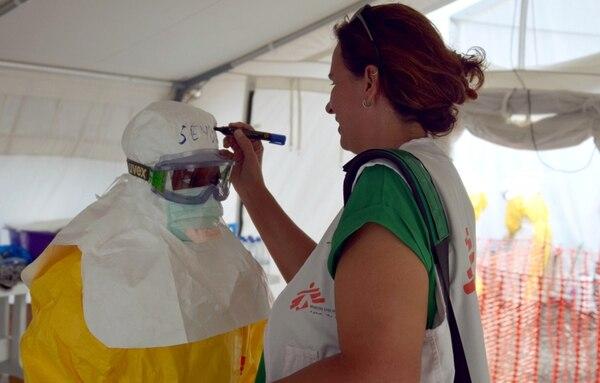 Una trabajadora de salud de la ONG Médicos Sin Fronteras escribió ayer el nombre de su compañera sobre el traje de protección que esta vestía. Esto ocurrió en el centro de tratamiento del ébola en Monrovia, Liberia.   AFP