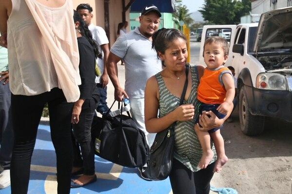 Johan, en brazos de su madre, Adalicia Montecinos, salía del albergue Casa Belén, en San Pedro Sula, Honduras, este viernes 20 de julio del 2018. Detrás, el padre, Rolando Bueso.