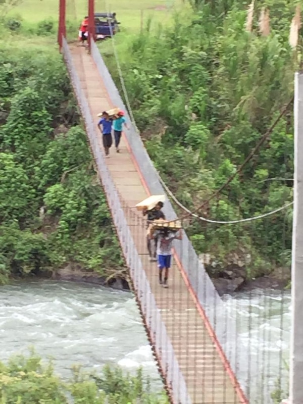 Los indígenas deben trasladar el material a través de un puente estrecho, que es el inicio de al menos dos horas de recorrido. Foto: Cortesía Wálter Brenes.
