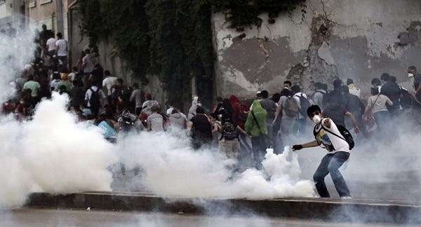 Mientras manifestantes escapan en medio de una nube de gas lacrimógeno ayer, cerca de la plaza de Taksim, en la ciudad de Estambul. | EFE