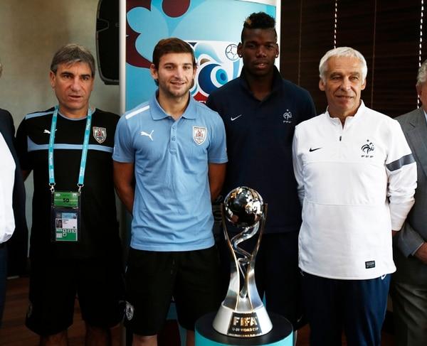 Juan Verzeri (izq.), D. T. de Uruguay, y su capitán, Gastón Silva, posan con el D. T. de Francia, Pierre Mankowksi (der.), y su capitán, Paul Pogba.   AP