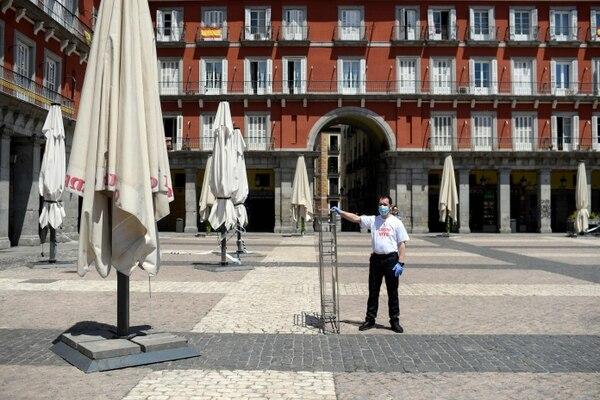 Un empleado instala el área de asientos al aire libre de un restaurante en la víspera de su reapertura en la Plaza Mayor de Madrid, el 24 de mayo del 2020, a medida que el país afloja lentamente un estricto bloqueo del coronavirus. Foto: AFP