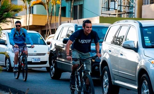 Personas en bicicleta usan la ciclovía en San José en medio de un pesado congestionamiento vial. Fotografía: AFP.