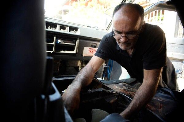 El mecánico Juan Carlos Rojas, quien labora en Belén de Heredia, examina un vehículo que asegura fue afectado por el nuevo désel, en la bomba de inyección. Foto: Diana Méndez.