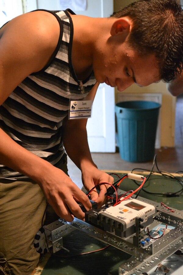 Marlon Varela ganó bronce en la Olimpiada de Química en Rusia. Jam Paniagua pone a prueba un robot que hizo en el Campamento Nacional Juvenil de Ciencias 2013.   FOTOGRAFÍAS CORTESÍA DE ROBERTO VEGA Y DE NATIONAL YOUTH SCIENCE CAMP.