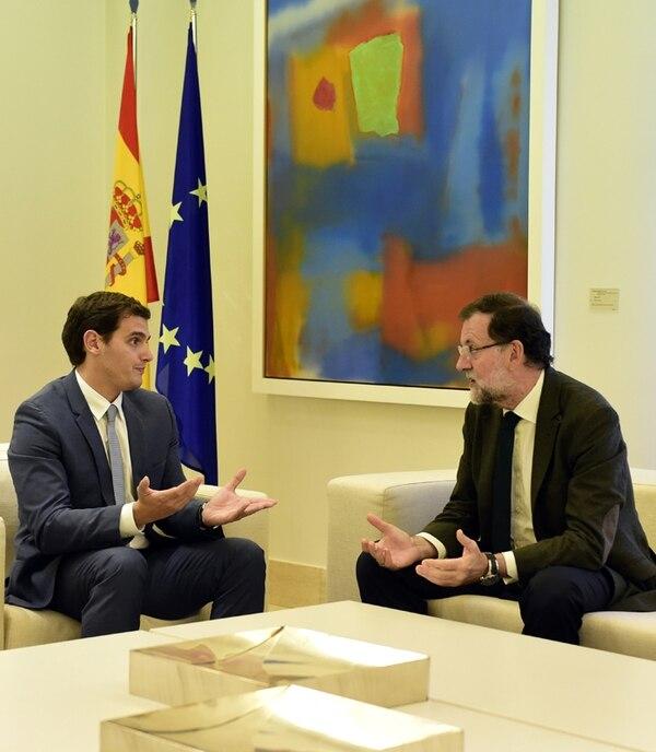 Mariano Rajoy (der.) habla con el opositor Albert Rivera. | AFP