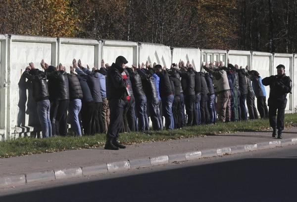 Agentes de policía vigilan a varios detenidos en el distrito Biryulovo en el suroeste de Moscú (Rusia), luego de que detuvieran al menos a 1.200 inmigrantes.