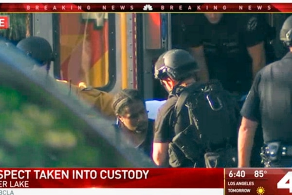 In this image from video provided by KNBC-TV, a suspect waits to be placed in an ambulance outside a Trader Joe's supermarket in the Silver Lake district of Los Angeles Saturday, July 21, 2018. (KNBC-TV via AP)