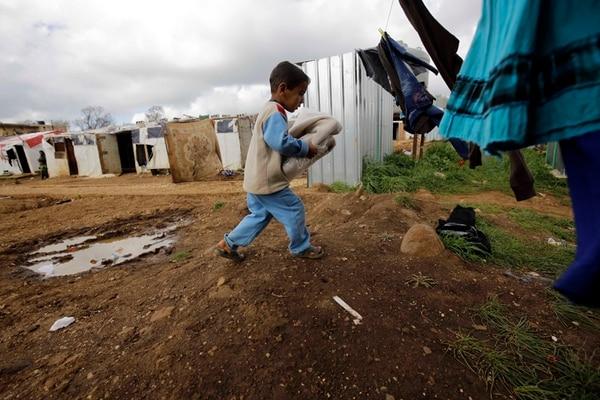 Un niño sirio lleva a su casa ropa donada por el gigante textil español Inditex y distribuida por grupos locales en al-Bireh, norte de Líbano. | AFP