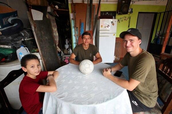 Anthony Contreras, en su hogar en Lomas de Pavas, en San José, junto a sus hermanos Gabriel (izquierda) y Rubén (derecha). Fotografía: John Durán