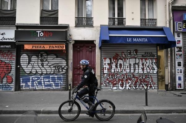 Un policía en bicicleta patrulla cerca de las tiendas cerradas cerca de la estación de tren Gare du Nord en París, el 17 de marzo del 2020, mientras que un bloqueo estricto entra en vigencia en Francia para detener la propagación del covi-19. Foto: AFP