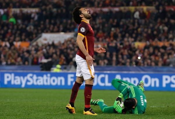 Keylor Navas toma un balón ante el acecho de Mohamed Salah.