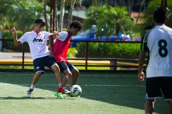 Jóvenes de la Academia Wílmer Pato López, ubicada en La Plywood de Alajuela, se entrenaron ayer en una de las canchas sintéticas del complejo. El juego en corto es una de las prioridades ahí. | JOSÉ CORDERO