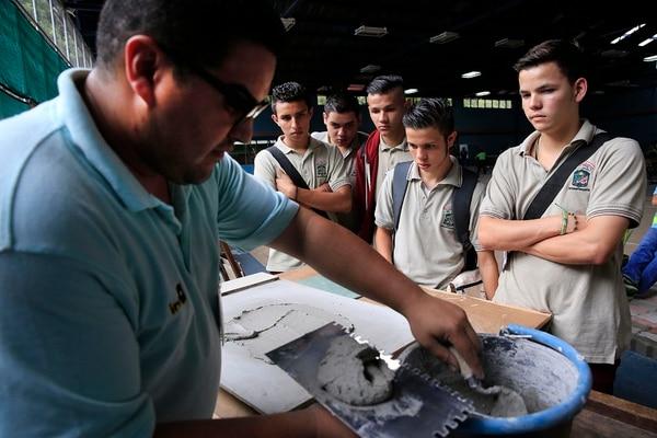 Rafael López Rodríguez, del núcleo de Tecnología de Materiales del INA, mostró a los Alumnos del Colegio Técnico Profesional de Dos Cercas de Desamparados, la colocación de una pieza de cerámica. Foto: Rafael Pacheco