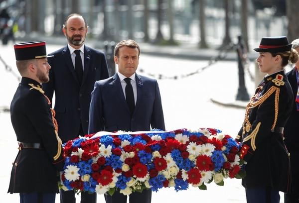 El presidente francés Emmanuel Macron (frente) y el primer ministro francés Edouard Philippe asisten a una ceremonia para conmemorar el final de la Segunda Guerra Mundial, en el Arco del Triunfo, en París, el 8 de mayo del 2020. Foto: AFP