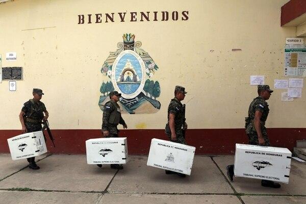 Militares hondureños llevaron las cajas con el material electoral a los centros de votación, ayer, en Tegucigalpa (izq.). El nacionalismo estuvo presente en la víspera de los comicios (der.).   AFP