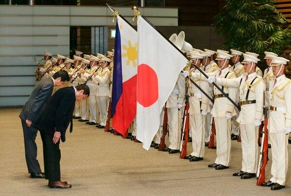 El presidente de Filipinas, Rodrigo Duterte (der.) saluda las banderas de Filipinas y Japón junto al Primer Ministro japonés Shinzo Abe (izq.) en Tokio, este miércoles 26.