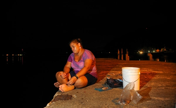 Juanita Sequeira va cada noche a pescar al atracadero de Golfito con la fe de conseguir algo que llevar a su madre y sus dos hijos.   MAYELA LÓPEZ