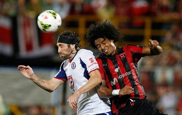 Mariano Pavone del Cruz Azul y Porfirio López disputan un balón en un encuentro de 'Concachampions'.