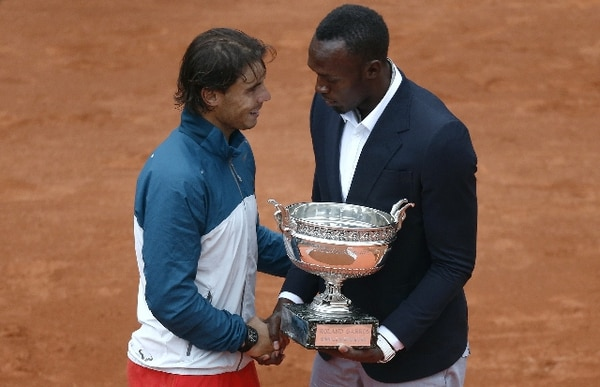 Bolt le entrega a Nadal el trofeo de Roland Garros.   AFP.