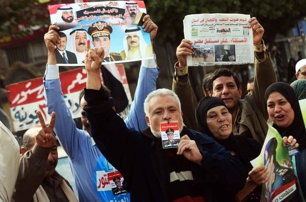 En las afueras de un recinto electoral en Kafr el-Sheikh, los votantes muestran carteles con la imagen del general Abdel Fatah al Sisi y líderes árabes. Al Sisi podría postularse como candidato a la presidencia.   AFP