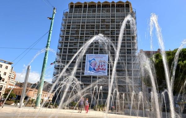 Un cartel con la imagen del papa Francisco colgaba ayer en una construcción en Cagliari, Italia, donde el Pontífice celebrará hoy una misa. | AFP.