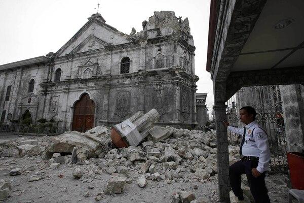 Un guarda cuida la basílica del Santo Niño, una de las iglesias más viejas y ahora en ruinas a raíz del terremoto que sacudió a Filipinas el martes. | AP