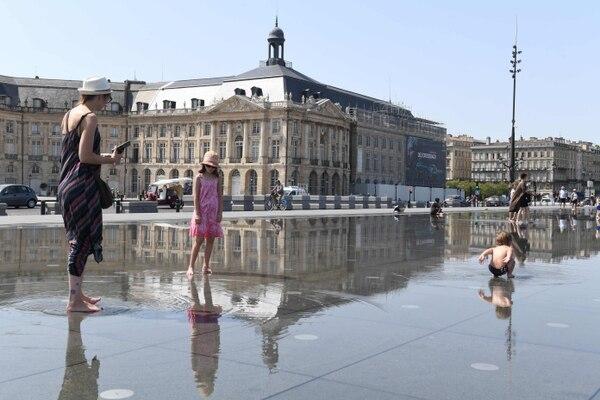 Niños se divertían en el Espejo de Agua de la plaza de la Bola en Budeos, Francia, este martes 23 de julio del 2019. En esa ciudad la temperatura alcanzó 42 °C.